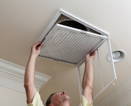 Man changing air conditioner air filter in ceiling