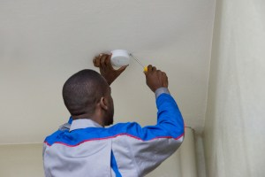 A man installs a new smoke alarm.