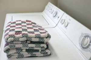 Clean, folded towels are shown on top of a dryer.