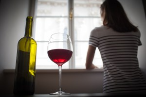 A woman gazes out a window with a nearly empty wine bottle nearby.