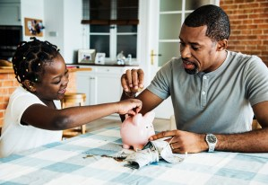 A father and his daughter place money in a piggy bank.