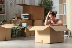 A tired-looking woman packs a box of belongings.