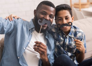 A father and son have fun with moustache masks.