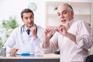 A doctor encourages an older man to quit smoking.