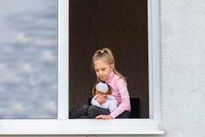 A girl holds a toy dog while sitting on the edge of a window.