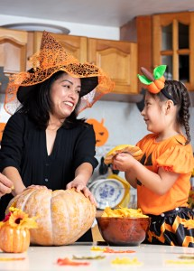 A mother and daughter carve a pumpkin in a kitchen.