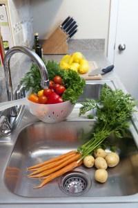 Vegetables in a colander in a kitchen sink.