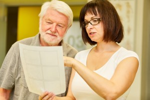 A naturopathic doctor reviews a chart with an older male patient.