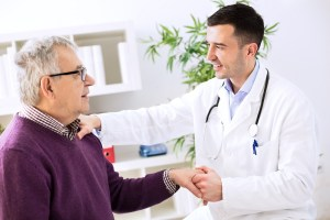 A male naturopathic doctor greets an older male patient with a handshake.