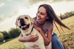 A woman hugs her Labrador dog in a grassy park.
