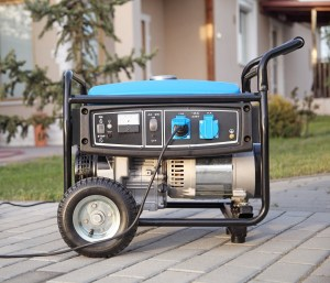 A small portable home generator sits on a brick walkway.