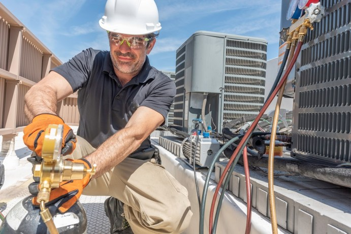 An air-conditioning contractor wearing safety gear installs a new unit on top of a high-rise roof.