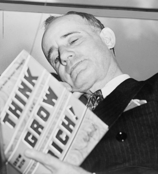 Napoleon Hill reads a copy of Think and Grow Rich