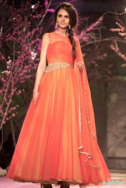 Soft orange anarkali with yellow fabric peeping from underneath