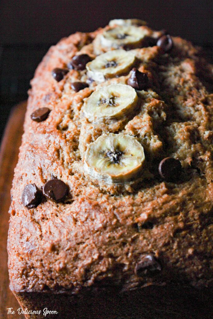 a loaf of banana bread riddled with chocolate chips and decorated with some sliced bananas