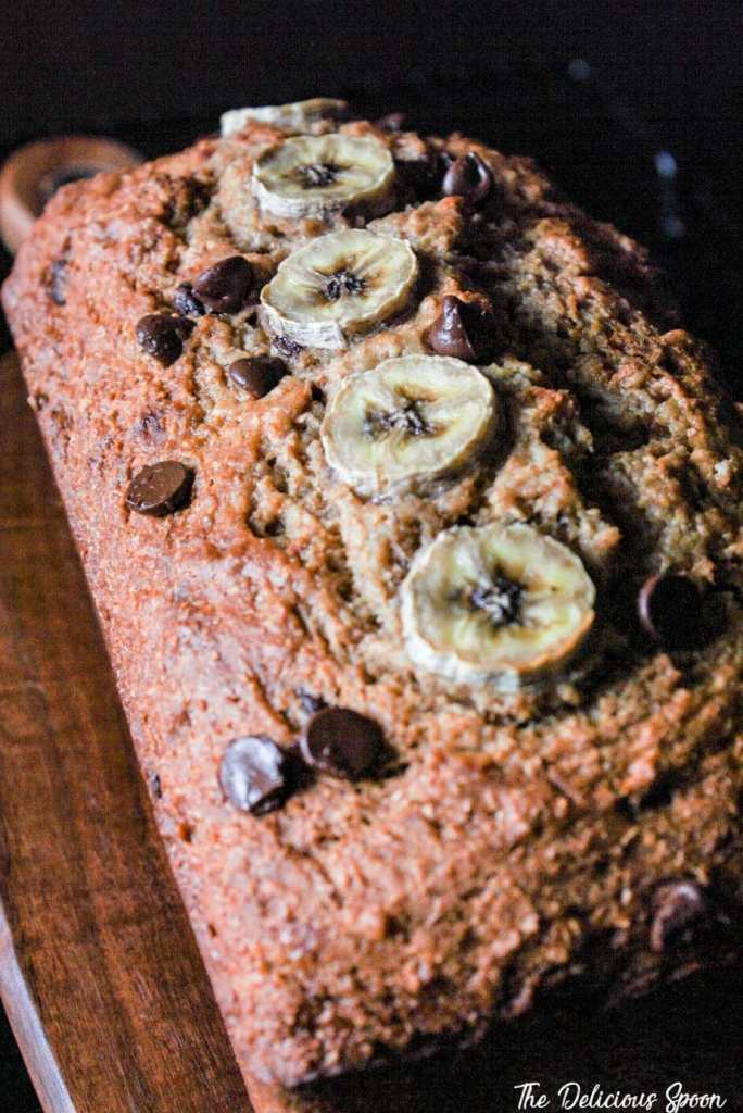 A fresh baked loaf of chocolate chip banana bread with decorative banana slices on top