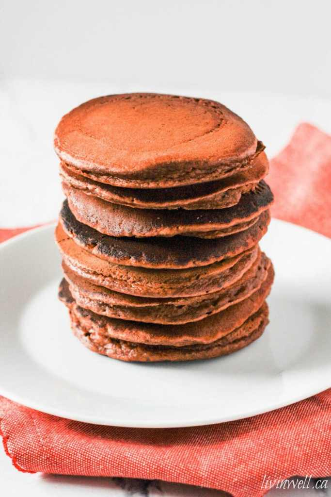 A big stack of hot off the grill Peanut Butter Protein Pancakes served on a white plate over a red napkin
