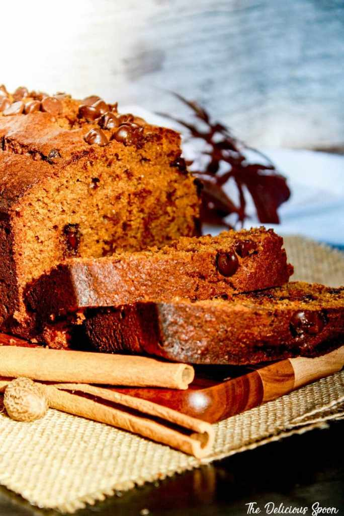 Slices of thickly cut Chocolate Chip Pumpkin Bread sprawled out on a wood cutting board surrounded with cinnamon, nutmeg on top of a burlap cloth
