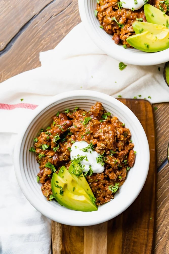 Overhead shot of a bowl of Crockpot Chili garnished with sour cream and avocado in a white bowl on a wood table