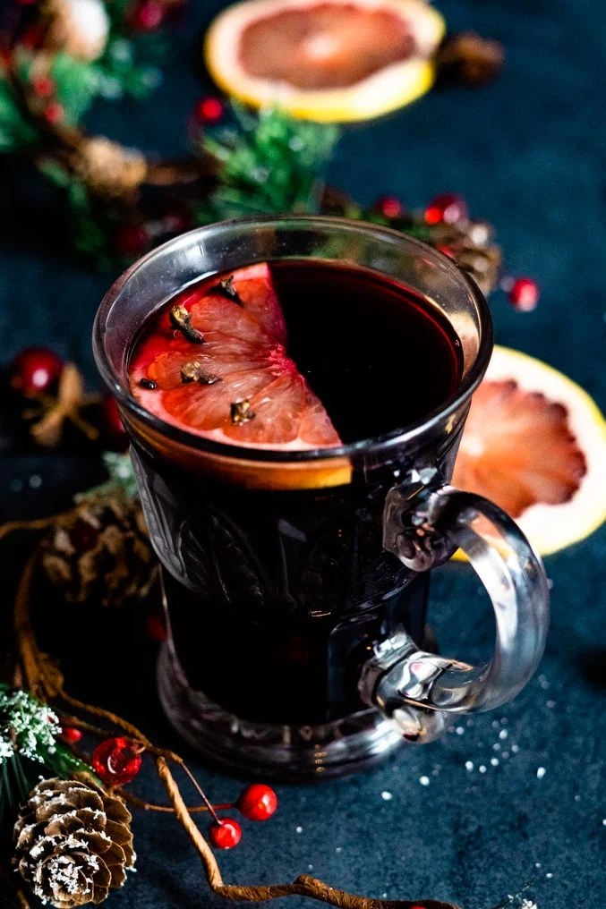 Close up of a cup of Mulled Wine with a slice of grapefruit decorated on a holiday table.