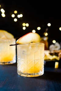 A Holiday Cocktail with a pear for decoration on a dark tablescape