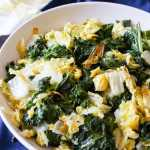 A colourful bowl or roasted kale and nappa cabbage on top of a dark blue napkin inside a white bowl