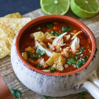 Chicken Tortilla soup served in a clay bowl with tortilla chips and limes