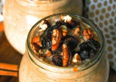 Two heaping mason jars of pumpkin pie overnight oats topped with raisins and chopped pecans