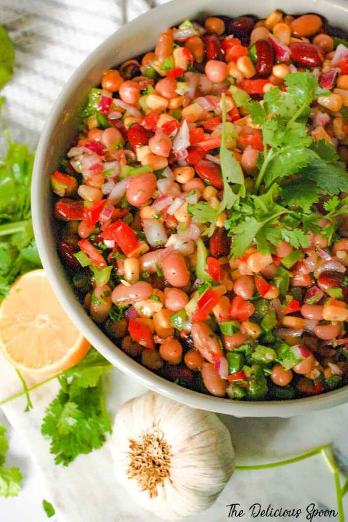A bowl of Mexican Bean salad filled with a mix of chopped fresh veggies and mixed beans and topped with a fresh sprig of cilantro.