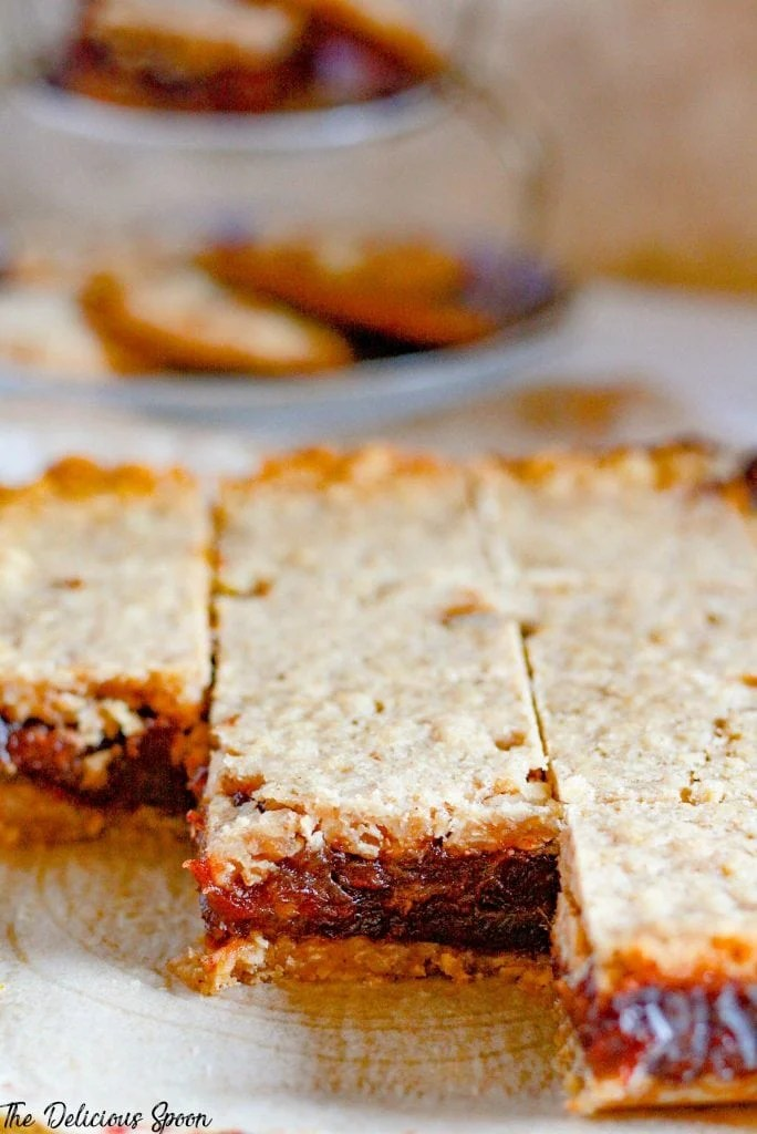 A sheet of date squares cute into pieces on a piece of parchment paper showcasing the sweet date filling and crunchy crumble crust
