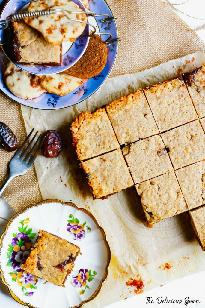 An overhead shot of a table spread with an assortment of cookies and date squares.