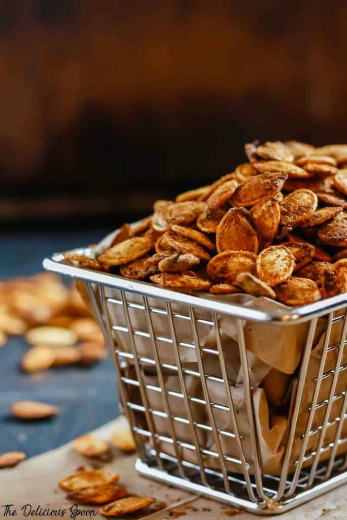Roasted pumpkin seeds in a small metal basket