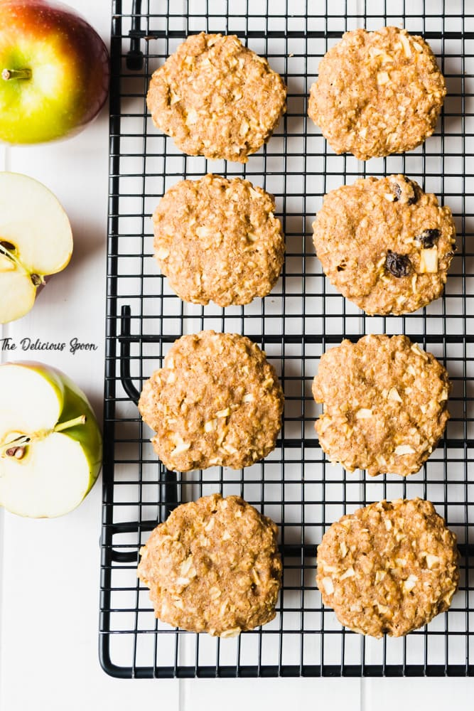 Overhead shot of apple oatmeal raisin cookies on a cooling rack with some cut apples off to the side