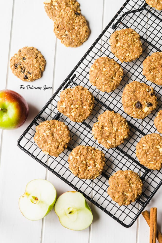 Apple Oatmeal Raise Cookies on a cooling rack surrounded by cut apples and more cookies