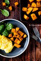 Overhead shot of a baking sheet of baked sweet potatoes and a plate of eggs