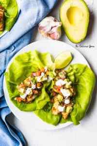 A plate of my Baja Fish Tacos Recipe alongside a blue napkin and avocado