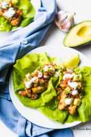 Two plates of Baja Fish Tacos on white plates with a blue napkin