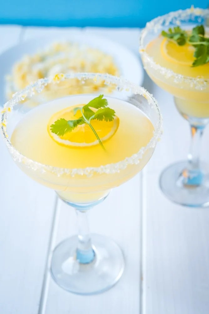 Shot of a Simple Margarita Recipe made with fresh Meyer Lemons in a margarita glass rimmed with salt, sugar and lemon zest.