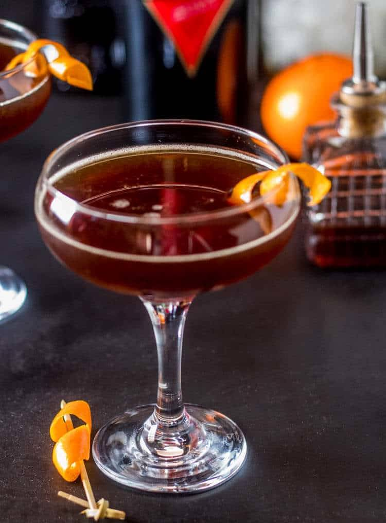 Mid-Summer Cocktail in a champagne glass decorated with an orange twist on a dark backdrop