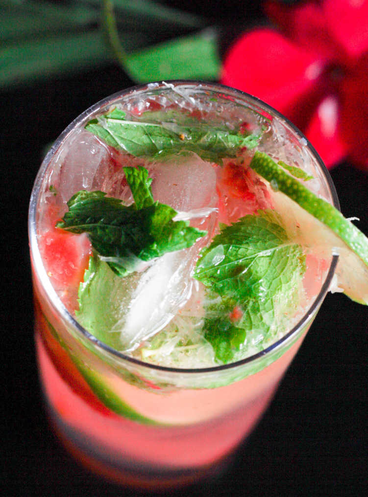 Strawberry Mojito in a tall glass from overhead on a black background beside a red tropical flower