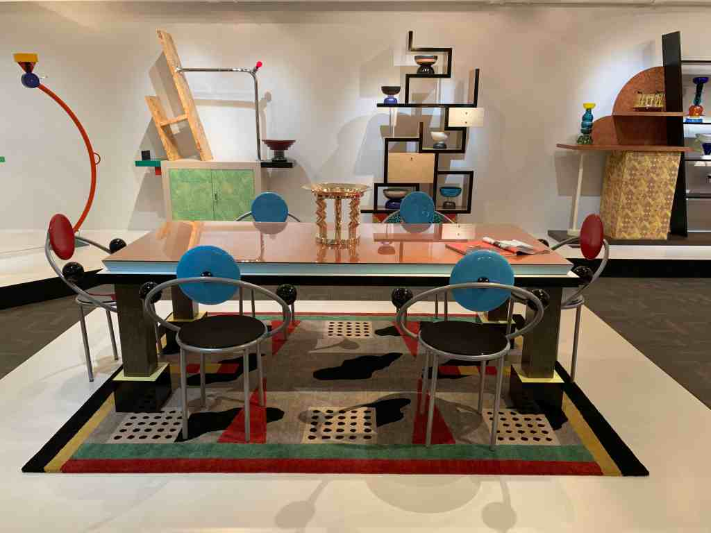 Palm Springs, 1984 by Ettore Sottsass. This table from the Memphis Group collection is crafted of wood and laminate with boldly contrasting colors. Also pictured are First chairs, 1983 by Michele de Lucchi made of enameled wood and metal. The First chair was introduced in the group's third collection. It is the only Memphis design mass produced. Its ergonomic back and elbow rests have the appearance of orbiting planets. Photo credit: The Design Tourist