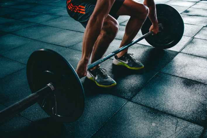person holding barbell, workout with best fitness apps