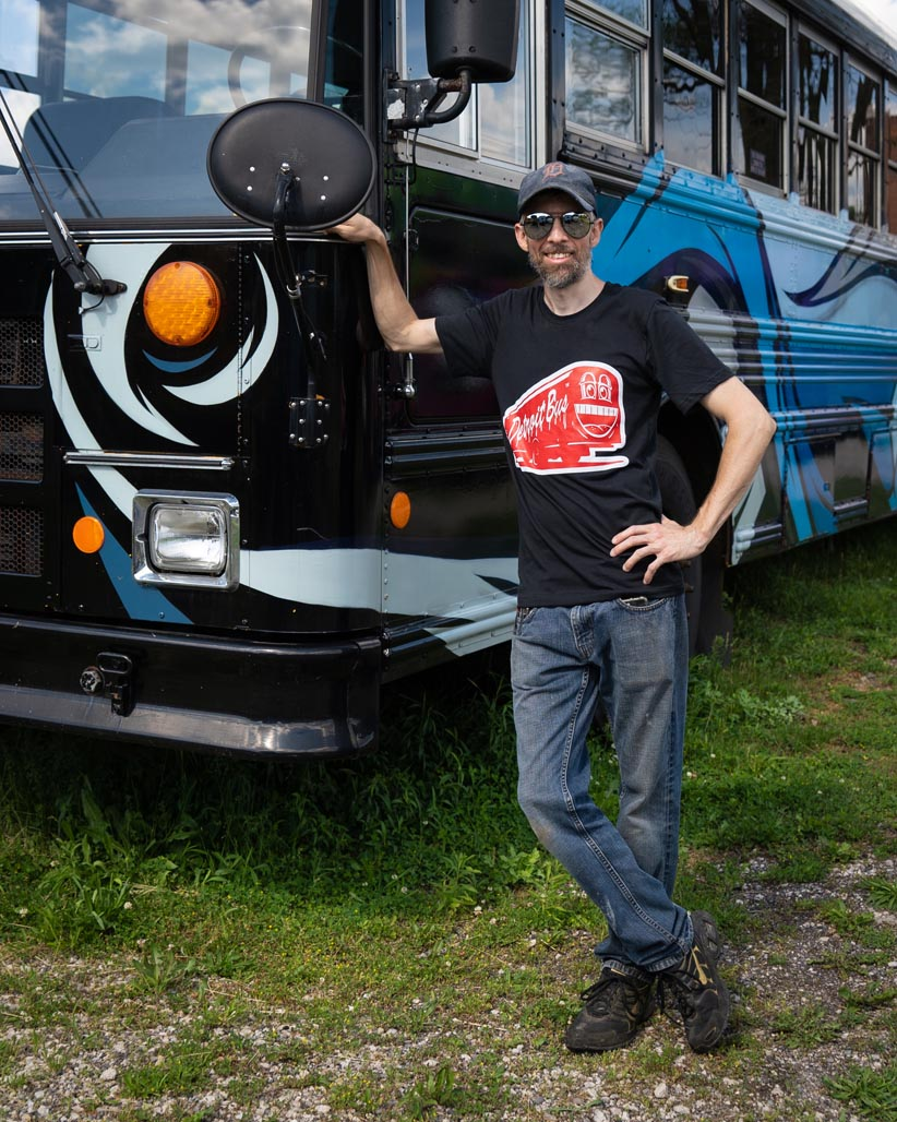 Person wearing art bus smile t-shirt leaning on another art bus