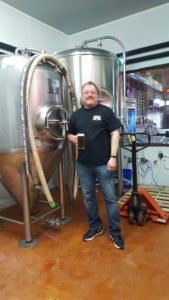 Chris Verich standing with his brewing equipment