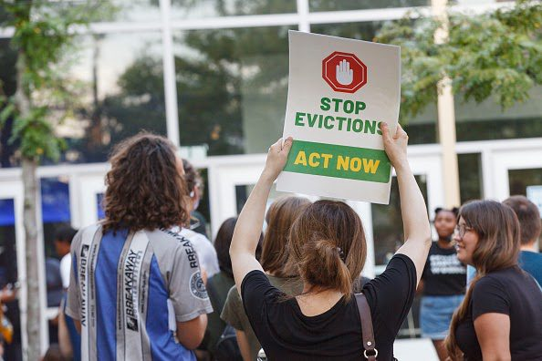 """A woman holds up a poster that says: """"Stop evictions. Act now."""""""