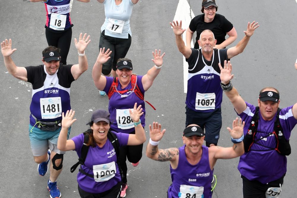 people running in Torbay Half Marathon waving upward