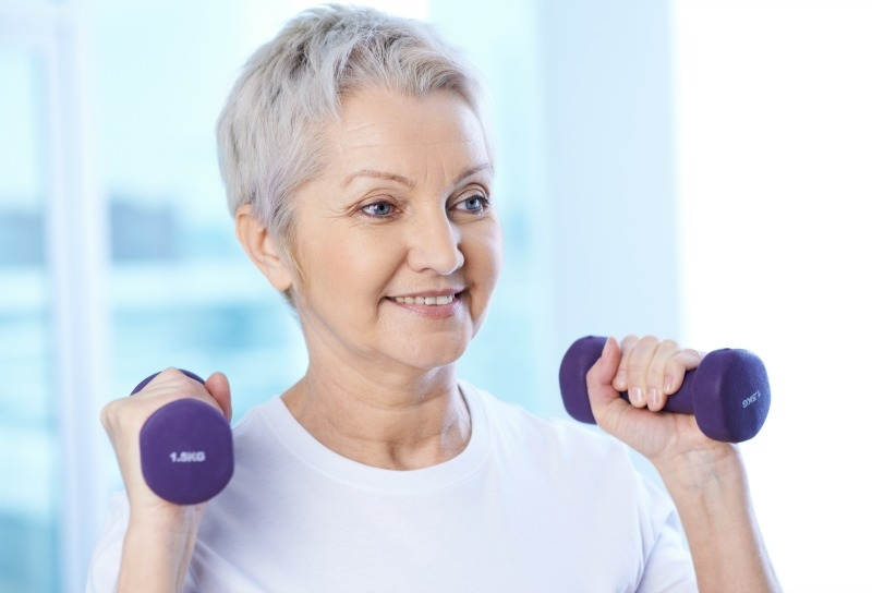 Portrait of pretty senior woman exercising with dumbbells