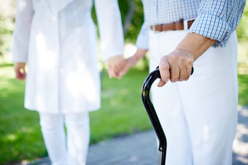 A caregiver holding the hand of her patient while walking outdoors