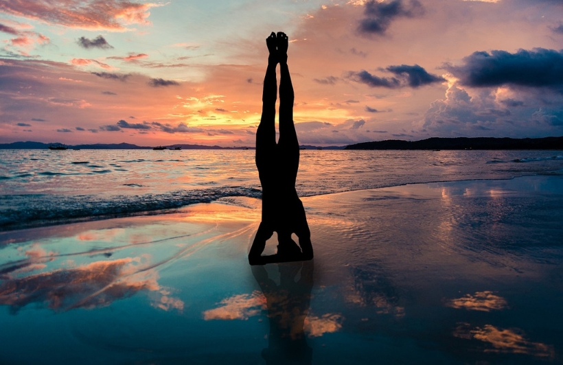 woman doing headstand at the beach