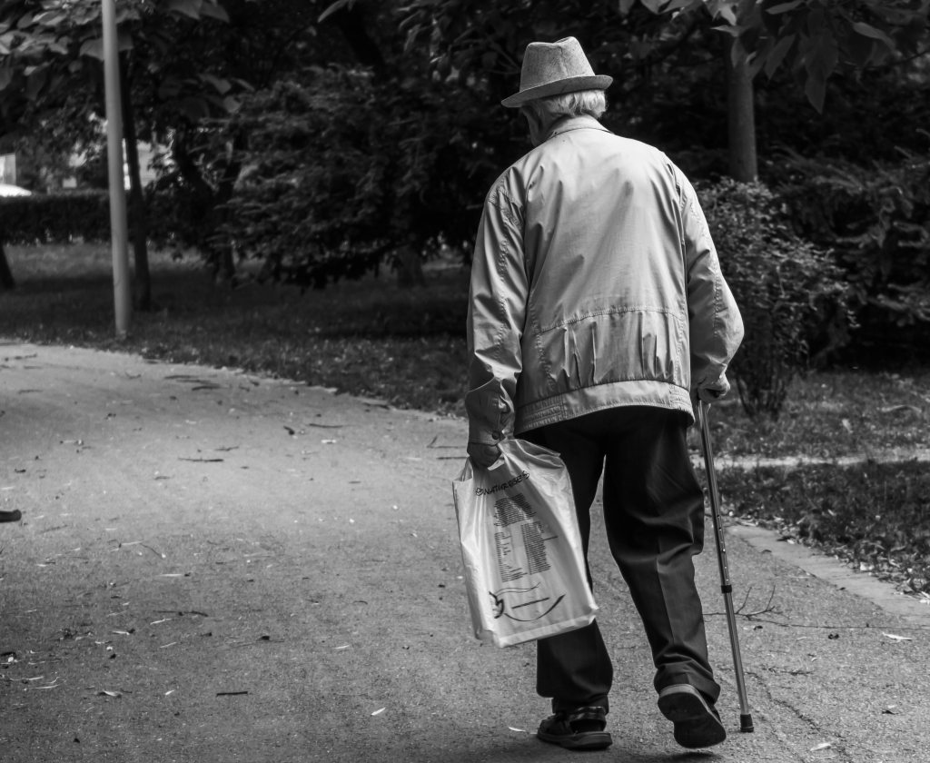 senior male walking with a cane caring a small bag.